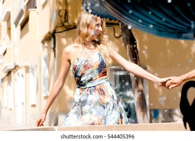 Young girl weared in dress holding her boyfriend's hand and smiling. Couple on a date in sunny summer date