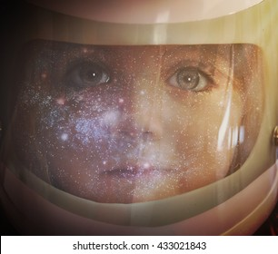 A young girl is wearing an astronaut helmet and looking into space with stars for an education, science or imagination concept.