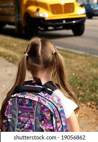 young girl wearing a backpack and waiting for school bus