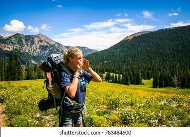 Young girl wearing backpack yodels across Grand Teton Mountains covered in wildflowers.