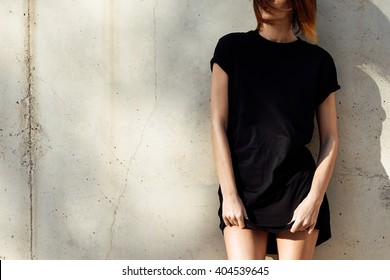 young girl wearing in a black blank t-shirt standing on a background of concrete wall. Sun rays