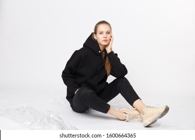 Young girl wearing blank and oversize black long hoody and balck jeans pants . Sitting on white background. Isolated.