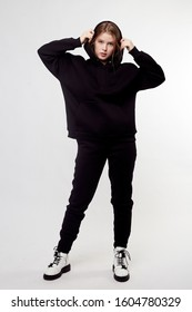 Young girl wearing blank and oversize black long hoody, black pants, white boots. White background.