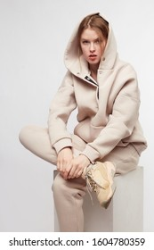 Young girl wearing blank and oversize beige long hoody, beige pants, beige sneakers . Sitting on white cube. White background.