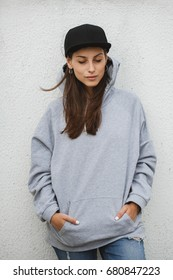 Young girl wearing blank and oversize long hoodie and black cap. Outdoors lifestyle portrait