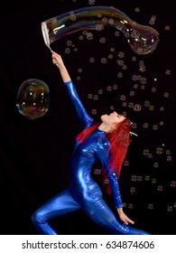 A young girl is wearing a blue catsuit and wears a flowered ear head band.  Surrounded by soap bubbles she plays  around with soapy water and forms large soap  bubbles in front of a black background.