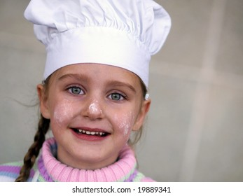 a young girl wearing a chef's hat