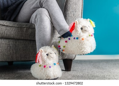 Young girl is wearing cute soft 3d llama slippers, while reading on the grey armchair