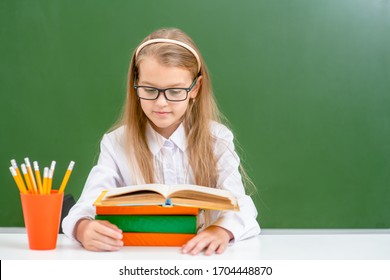 Young girl wearing eyeglasses reads book near empty green chalkboard. Empty space for text