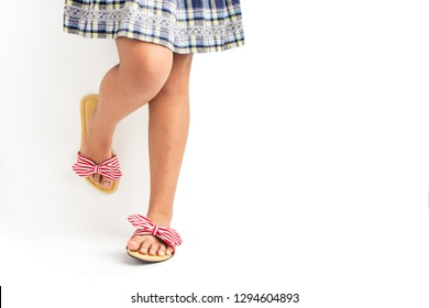 Young girl wearing fasionable stripy sandals and dress with white background for copy space.