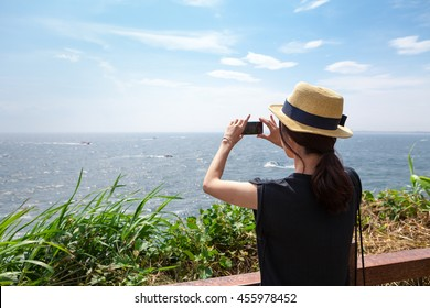 Young girl wearing hat taking picture of seascape during summer with her smartphone
