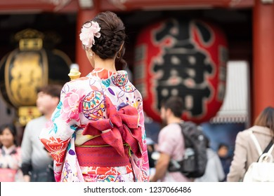 """Young girl wearing Japanese kimono standing in front of Sensoji Temple in Tokyo, Japan. Kimono is a Japanese traditional garment. The word """"kimono"""", which actually means a """"thing to wear"""""""