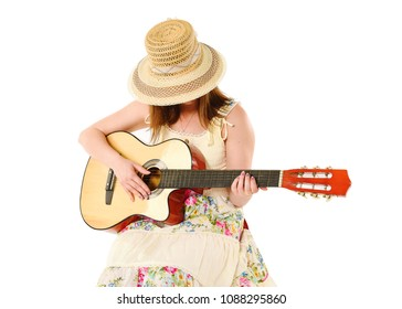Young girl wearing a lemon dress and pretty straw hat strumming a guitar. Taken in studio against white background. Space for text.