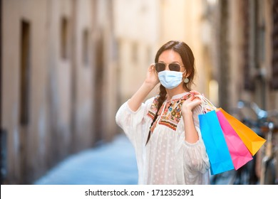 Young girl wearing a mask for prevent virus with shopping bags on narrow street in Europe.