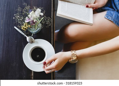 Young girl, wearing on blue shorts, sitting on beige leather sofa, reading a book and holding a cup of coffee, vase with flowers  standing on the dark wooden table, on cafe, close up. Point of view