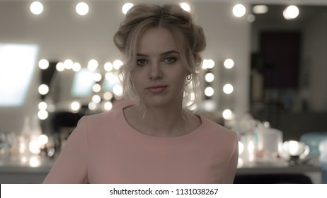 Young girl wearing pink dress with professional makeup look at camera