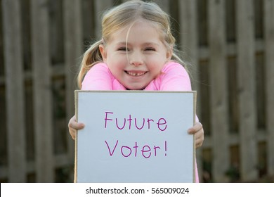 young girl wearing pink and holding sign that says Future Voter which symbolizes Women's rights