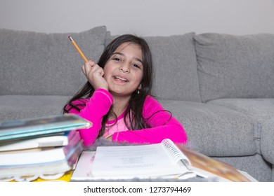 A young girl wearing a pink shirt is doing her homework holding a pencil