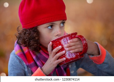 Young girl wearing red hat and scarf sipping hot tea out of a big red cup.