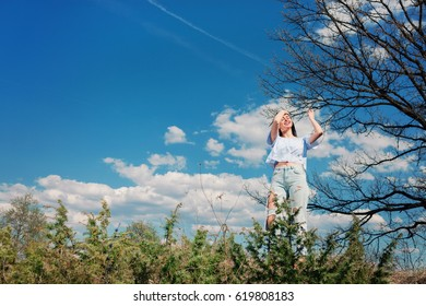 Young girl wearing ripped jeans posing in nature.