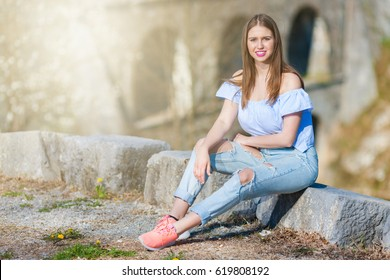 Young girl wearing ripped jeans sitting on the stone and posing for camera.  Sun leak added.