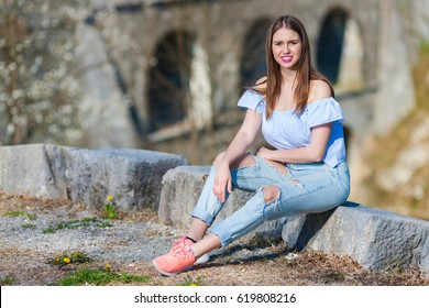 Young girl wearing ripped jeans sitting on the stone and posing for camera.