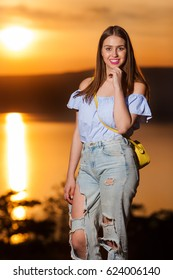 Young girl wearing ripped jeans and yellow handbag posing with sunset in background.