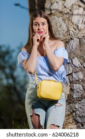 Young girl wearing ripped jeans and yellow handbag posing leaned on the stone wall.