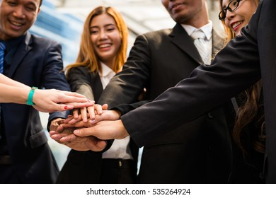 Young girl wearing suits handshake with her asian employee out of the office after meeting with big group company  in Asia. Every people very happy to do business together.