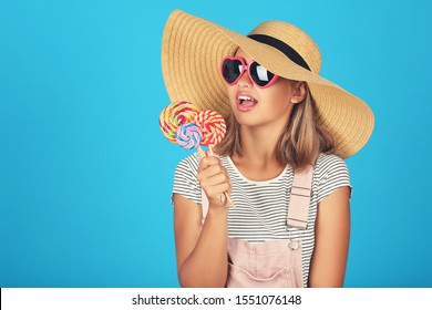 Young girl wearing sunglasses, hat and holding lollipops on blue background
