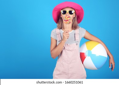 Young girl wearing sunglasses, hat and holding lollipop and inflatable ball on blue background
