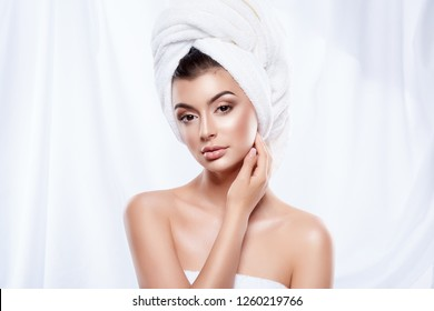 Young girl wearing white towel at white studio background, beauty photo, fresh skin, skin treatment concept, close up portrait.