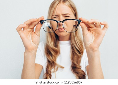 Young girl wearing white t-shirt, holding glasses, selective focus on glasses, standing on gray background, Concept: poor eyesight