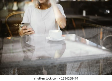 A young girl wearing white t-shirt is sitting in a cafe with a big cup of coffee or tea and looking into her smartphone behind a glass vitrine