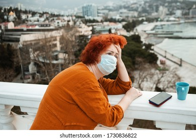 Young girl wears a protection mask and have a headache after working isolated on a rooftop. Prevent contact from the coronavirus. Concept of social distance.