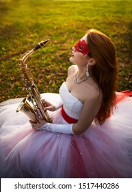 A young girl in a wedding dress with a red garter and a red lace mask, in an autumn park, with a saxophone in her hands, in profile.