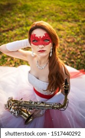 A young girl in a wedding dress with a red garter and a red lace mask, in an autumn park, with a saxophone in her hands.