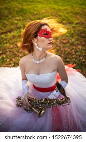 A young girl in a wedding dress with a red garter and a red lace mask, in an autumn park, with a saxophone in her hands. Girl shook her hair.