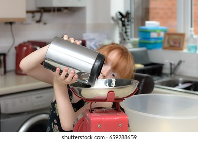 young girl weighing out sugar into red scales in kitchen environment. young girl baking cakes independently in her home ready for her party