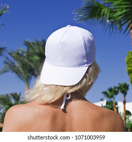 Young girl in a white baseball cap on a background of blue sky and palm trees. White baseball cap mockup. Close-up