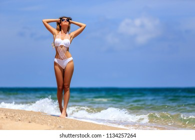 Young girl in white bikini enjoying at tropical beach, Phuket, Thailand