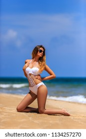 Young girl in white bikini posing at tropical beach, Phuket, Thailand
