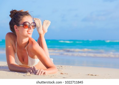 young girl in white bikini tanning at tropical beach