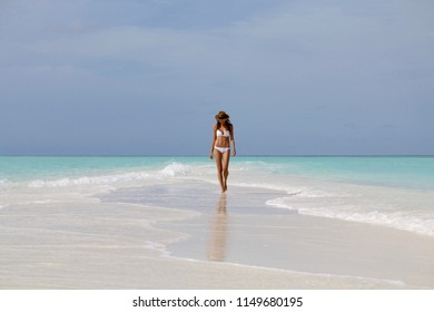 Young girl in white bikini walking on the beach in Madives