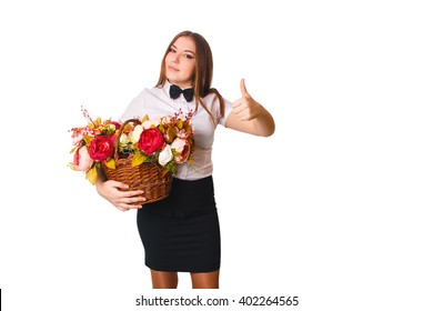young girl in white blouse holding a basket of flowers on a white background and showing sign yes, holiday, easter, flowers