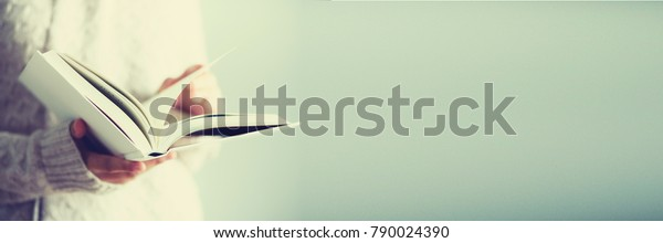 Young girl in white cardigan reading opened book. Copy space. lifestyle and school concept. Banner.