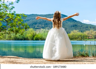Young girl in white communion dress with open arms at lake.