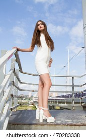 Young girl in a white dress and high-heeled shoes on the background of bridge structures