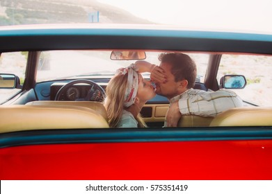 Young girl in white dress and man kissing on the front seats of the red car, seaside of Malta