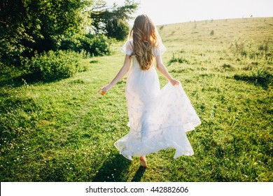 Young girl in a white dress in the meadow. Woman in a beautiful long dress posing in the garden. Stunning bride in a wedding dress